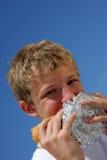 Um adolescente que morde em um sanduíche Fotos de Stock Royalty Free