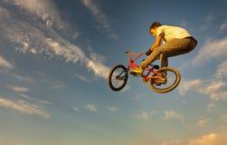 Um adolescente que salta em uma bicicleta imagem de stock