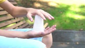 Um adolescente quebra um copo plástico branco com ambas as mãos filme