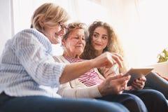 Um adolescente, uma mãe e uma avó com tabuleta em casa Imagem de Stock