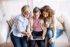 Um adolescente, uma mãe e uma avó com tabuleta em casa Fotografia de Stock Royalty Free