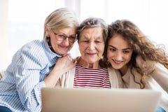 Um adolescente, uma mãe e uma avó com tabuleta em casa Imagens de Stock