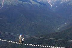 Um adulto e um movimento da criança sobre uma suspensão da ponte alta nas montanhas fotografia de stock