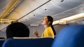 Um aeromoço fêmea está ajudando a um passageiro na classe de economia da rota Banguecoque foto de stock