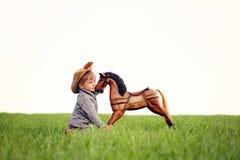 Um afago do rapaz pequeno ao cavalo de balanço de madeira imagens de stock royalty free