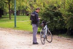 Um agente da polícia com uma posição da bicicleta no parque de Sempione próximo ao castelo de Sforzesco e a olhar o telefone celu fotografia de stock royalty free