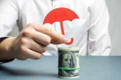Um agente de seguros guarda um guarda-chuva vermelho sobre notas de dólar Proteção das economias Mantendo o dinheiro seguro Inves imagem de stock