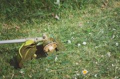 Um ajustador do cortador de grama encontra-se na grama no jardim Chanfro da grama, cortando gramados imagens de stock royalty free