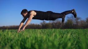 Um ajuste, homem atrativo vai exercitar em uma grama verde Faz impulso-UPS com mãos estendido Um fundo bonito filme