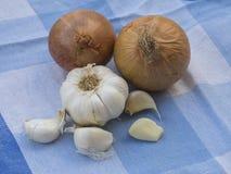 Um alho inteiro e cravos-da-índia de alho e de duas cebolas no whi azul foto de stock royalty free