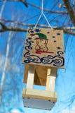 Um alimentador do pássaro com um telhado No telhado de uma figura tirada O animal descrito no tampão com uma vara curvada, em tor Fotografia de Stock Royalty Free