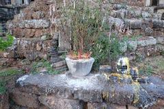 Um altar budista pequeno com lotes de varas do incenso Córregos derretidos congelados da cera imagens de stock
