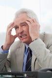 Um alto directivo tired que tem uma dor de cabeça foto de stock