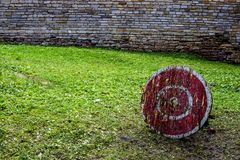Um alvo de madeira para uma besta com uma cor vermelha com círculos brancos no pátio de um castelo antigo do castelo Um gramado v imagens de stock