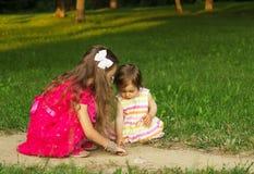 Um amor de duas irmãs mais nova e tem um divertimento no parque bonito no por do sol Foto de Stock