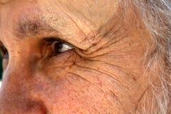 Um ancião com os enrugamentos profundos perto dos olhos olha na distância foto de stock