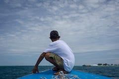 Um ancião que senta-se na curva do navio que aprecia a beleza do oceano azul Um guia local está guiando o turista em Harapan imagens de stock