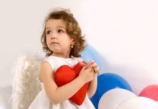 Um anjo pequeno com coração vermelho imagens de stock royalty free
