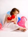 Um anjo pequeno com coração vermelho imagens de stock
