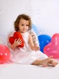 Um anjo pequeno com coração vermelho imagem de stock royalty free
