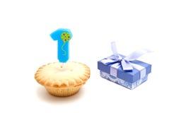 Um ano de vela do aniversário com queque e presente no branco Imagem de Stock