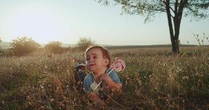 Um ano muito bonitos do bebê idoso que come muito engraçado um pirulito que estabelece na grama, por do sol surpreendente vídeos de arquivo