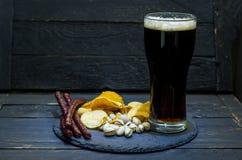 Um aperitivo da cerveja e uma cerveja variados Salsichas, microplaquetas e pistaches Fotos de Stock