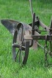 Um arado equestre velho na grama verde A faixa média de Rússia foto de stock