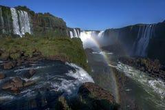 Um arco-íris forma sobre a Foz de Iguaçu magnífica em Brasil fotografia de stock royalty free