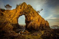 Um arco natural na costa na hora dourada imagens de stock