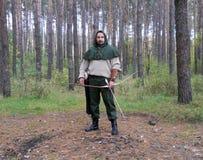 Um arqueiro encapuçado em uma madeira imagem de stock royalty free
