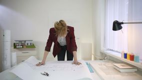 Um arquiteto fêmea que olha um modelo de uma casa filme