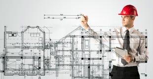 Um arquiteto novo que tira um plano da casa Fotos de Stock Royalty Free