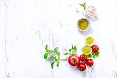 Um arranjo dos tomates, da manjericão, do azeite e do sal Himalaia fotografia de stock