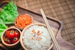 Um arroz branco na bacia e em hashis de madeira com cenouras, sésamo preto, e vegetais dos tomates na placa de madeira Imagens de Stock Royalty Free