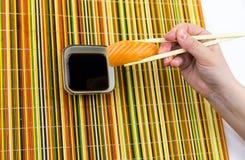 Um arroz de sushi delicioso e uma fatia de salmões, guardando as varas de bambu em sua mão, são abaixados em uma bacia com molho  Fotografia de Stock Royalty Free