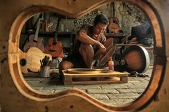 Um artesão da guitarra é ocupado fazer ordens de seus clientes imagens de stock