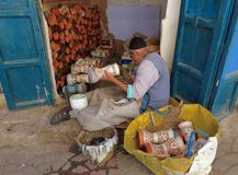 Um artesão idoso que envolve o couro em torno dos cilindros cerâmicos diminutos imagens de stock royalty free