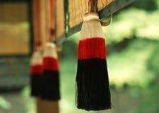 Um artigo decorativo tradicional de suspensão vermelho e preto japonês com o fundo verde borrado fotografia de stock
