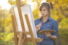Um artista da jovem mulher que está na frente de uma armação com uma escova e que pensa que uma menina pinta uma imagem na nature imagem de stock