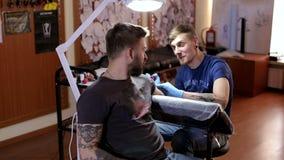 Um artista profissional da tatuagem faz uma tatuagem em um braço do ` s do homem em uma sala de estar da tatuagem video estoque
