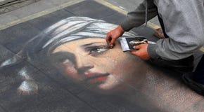 Um artista que pinta um retrato de uma menina imagens de stock royalty free