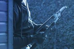 Um assaltante com um cortador de parafuso fotos de stock