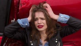 Um assento de grito da menina na terra perto de um carro quebrado, estava em um acidente video estoque