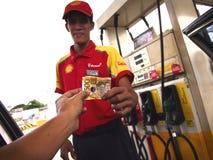 Um assistente da estação de gasolina recebe o pagamento de um cliente Imagem de Stock