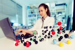 Um assistente de laboratório da mulher usa o computador para a simulação Imagens de Stock Royalty Free