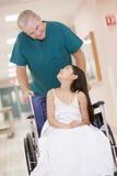 Um assistente hospitalar que empurra uma menina em uma cadeira de rodas fotos de stock