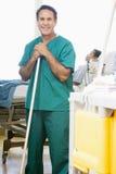 Um assistente hospitalar que esfrega o assoalho em um hospital Fotos de Stock Royalty Free