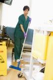 Um assistente hospitalar que esfrega o assoalho em um hospital Imagens de Stock Royalty Free