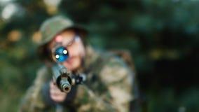 Um atirador furtivo em uniformes da camuflagem está apontando Esconder no arbusto video estoque